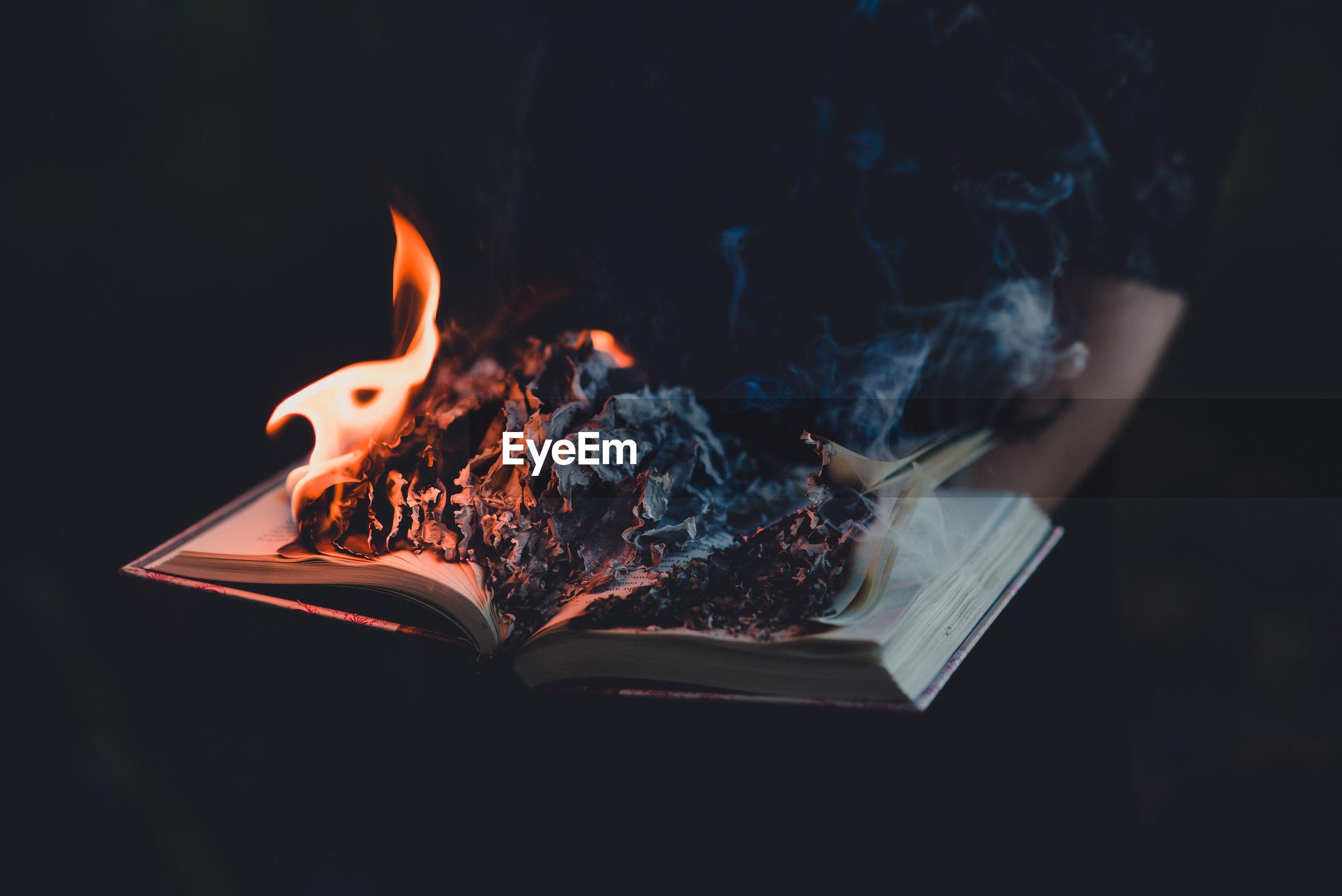 Burning book against black background
