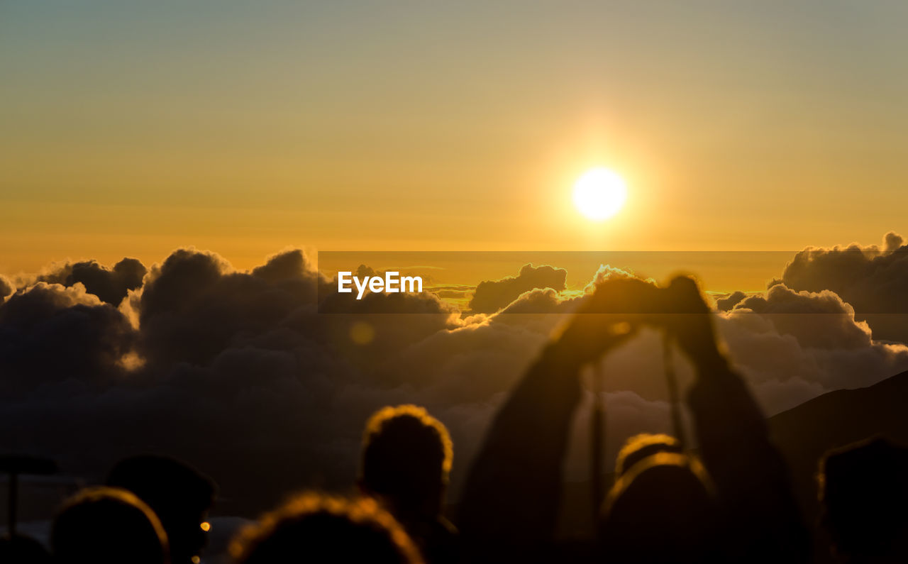 People photographing cloudy sky during sunrise