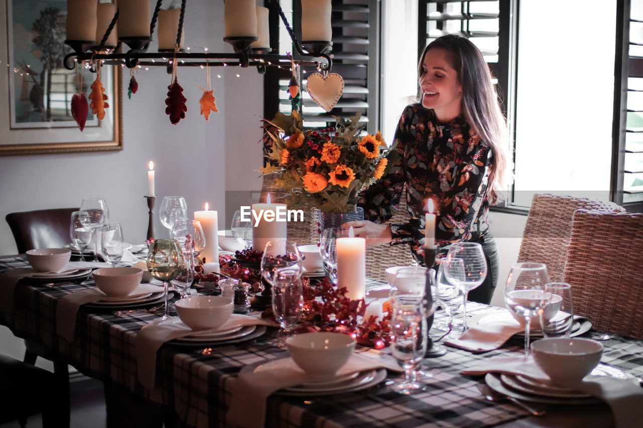 Smiling mid adult woman holding arranging flower vase on dinning table at home