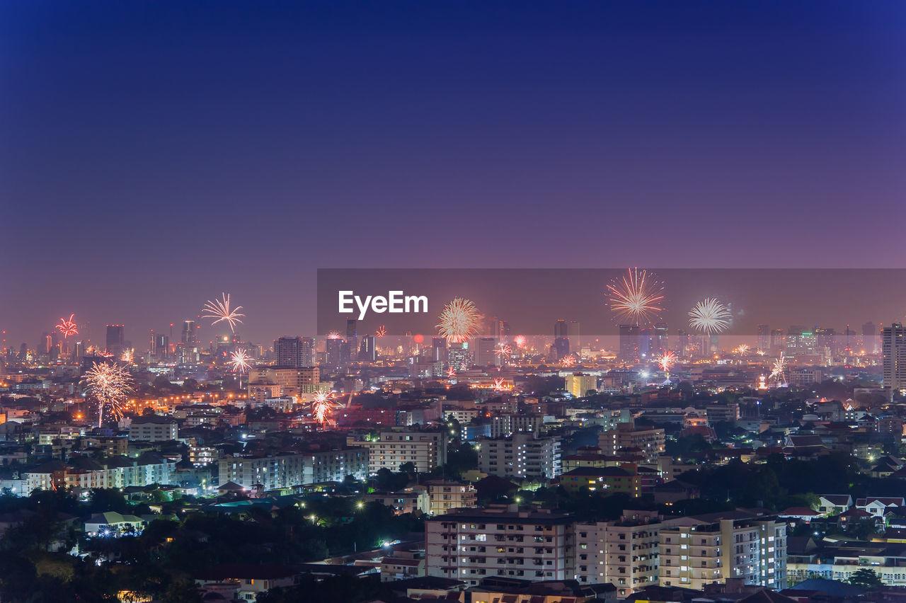 Firework Exploding Over Illuminated Cityscape At Night