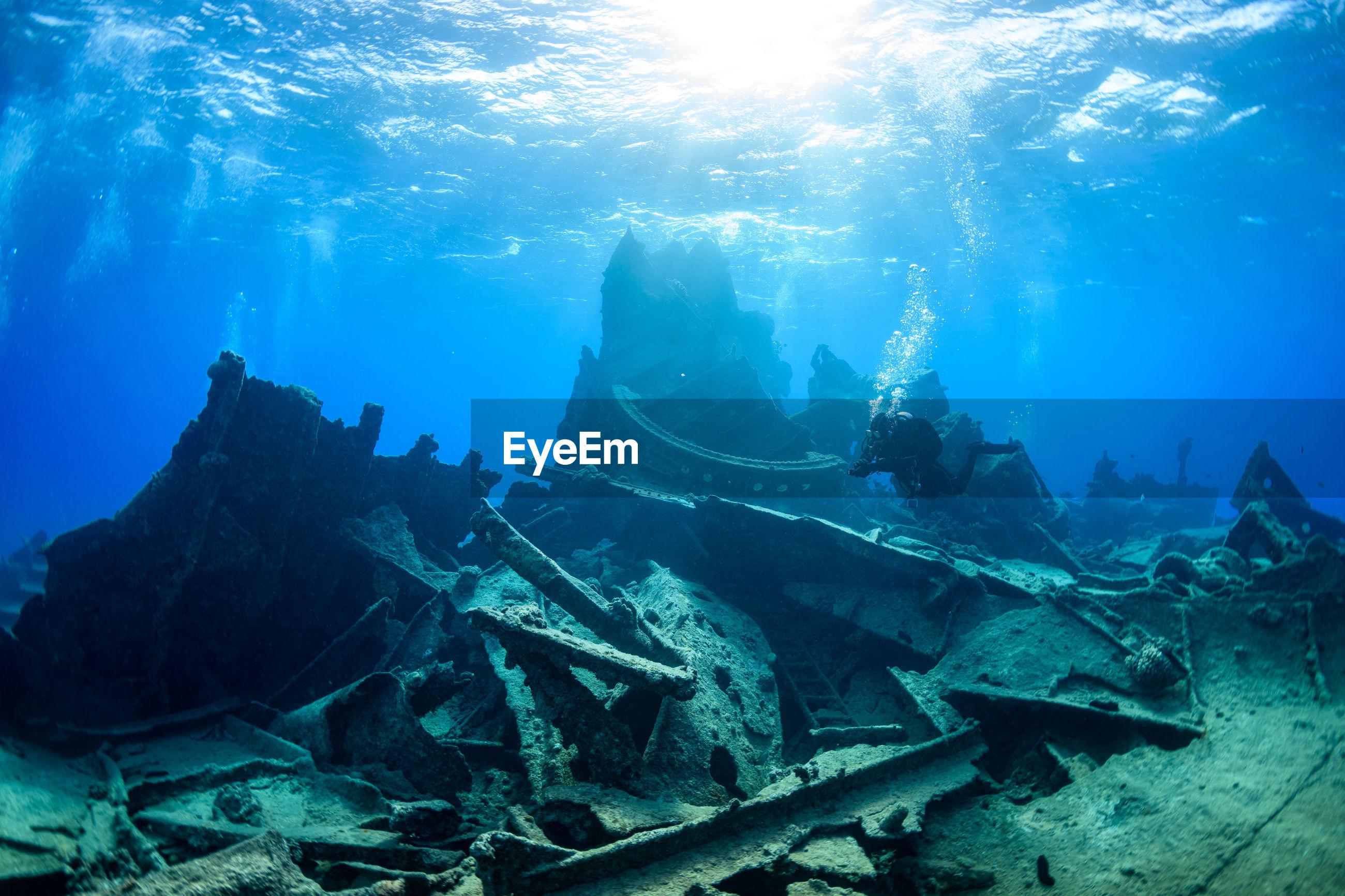 Woman scuba diving by shipwreck in sea