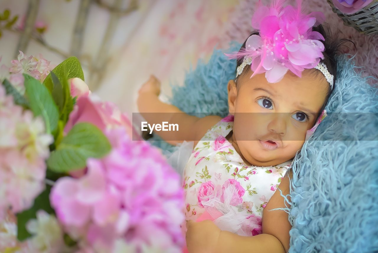 Cute baby girl lying on rug by decorations