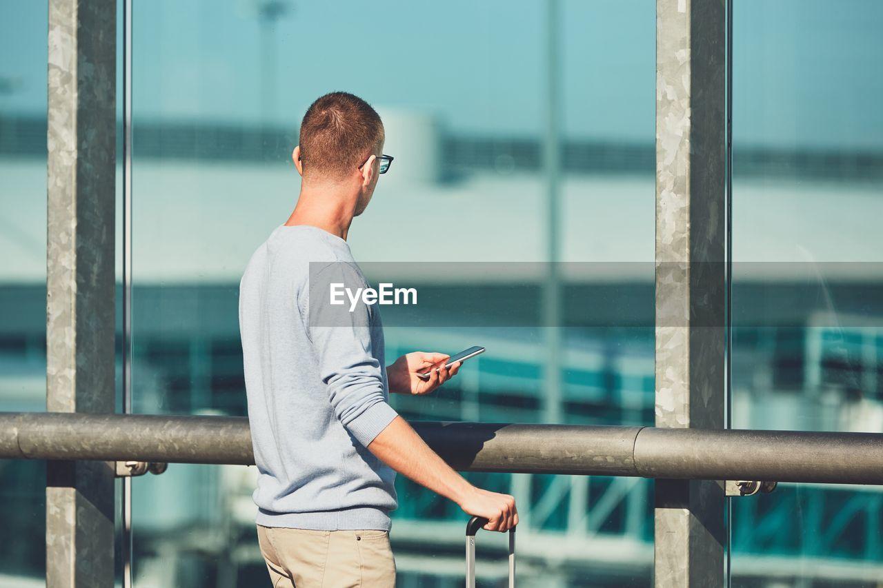 Close-Up Of Man Using Mobile Phone At Railing