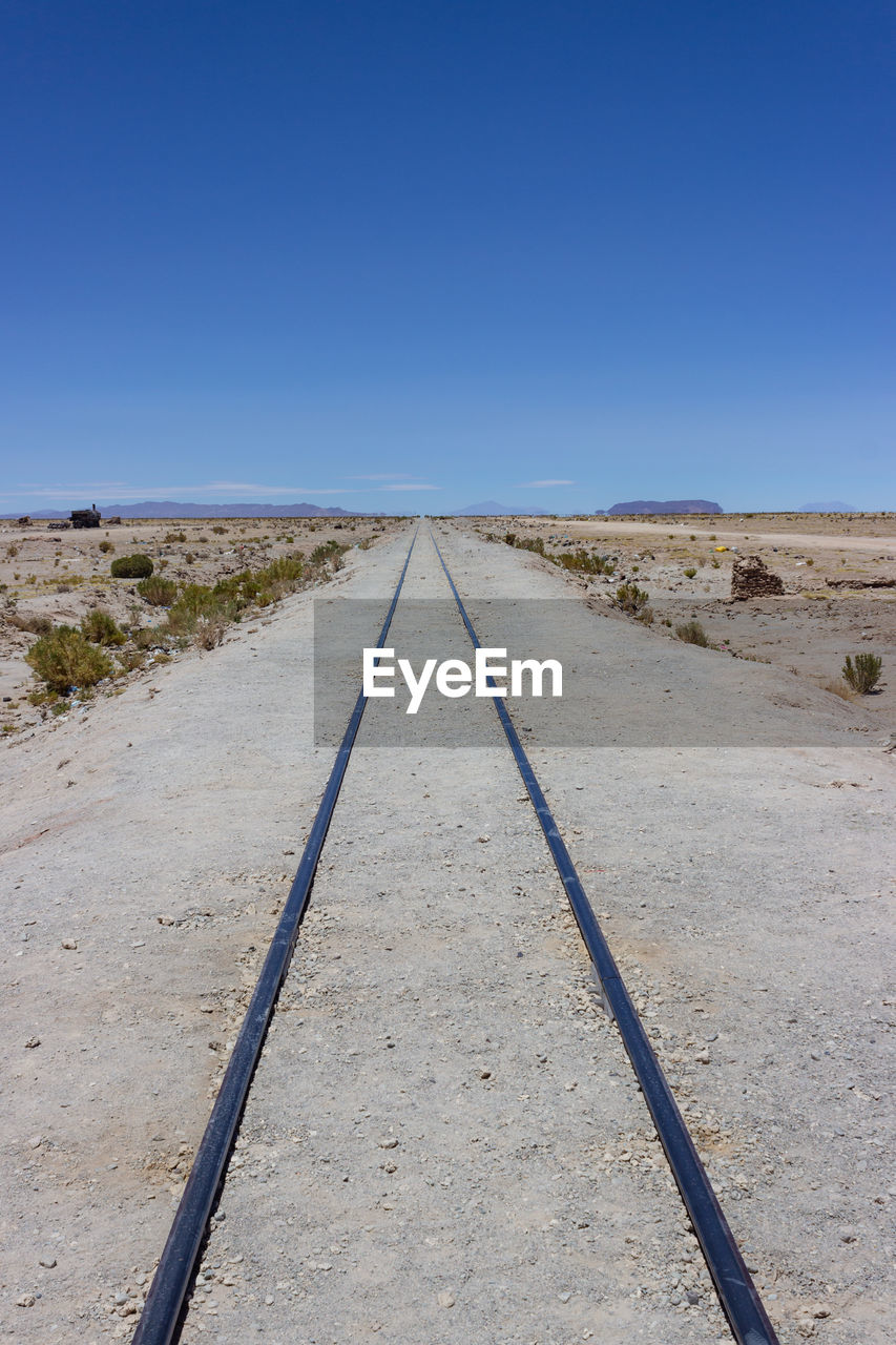 sky, clear sky, direction, the way forward, track, copy space, blue, rail transportation, nature, no people, railroad track, day, diminishing perspective, scenics - nature, land, transportation, tranquil scene, environment, tranquility, landscape, outdoors, arid climate, climate, long