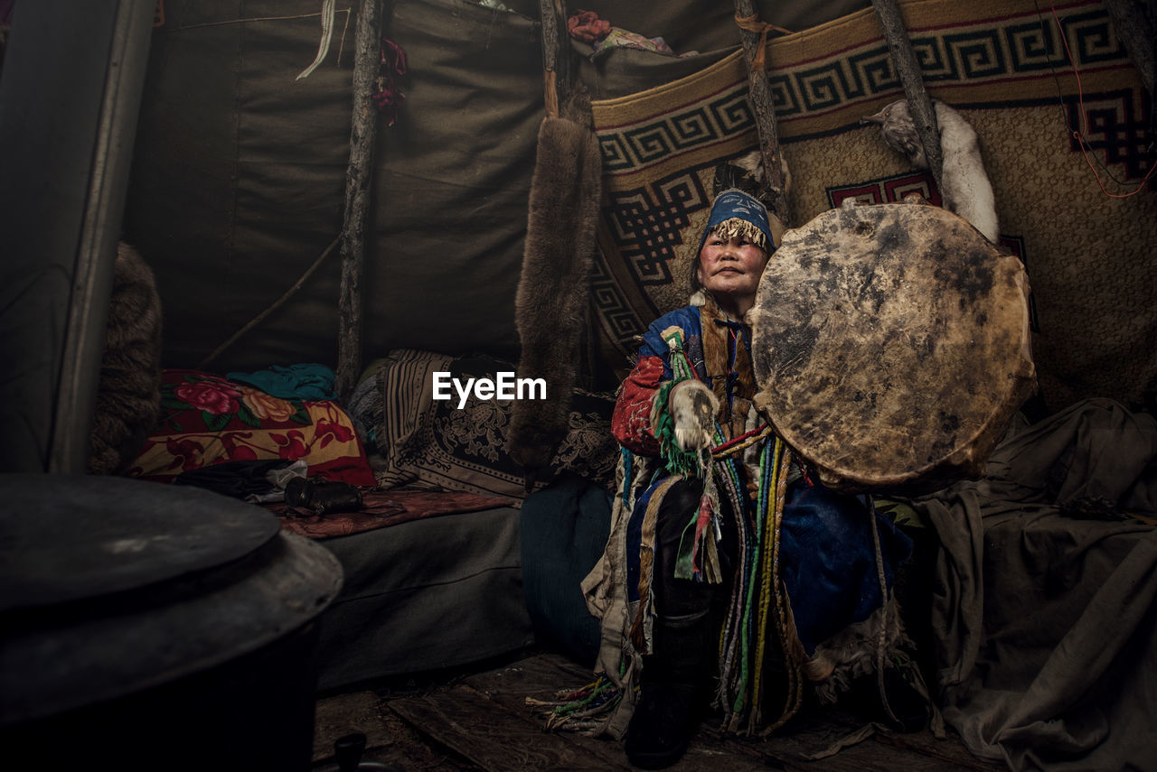 Woman Wearing Traditional Clothing Holding Shield In Tent