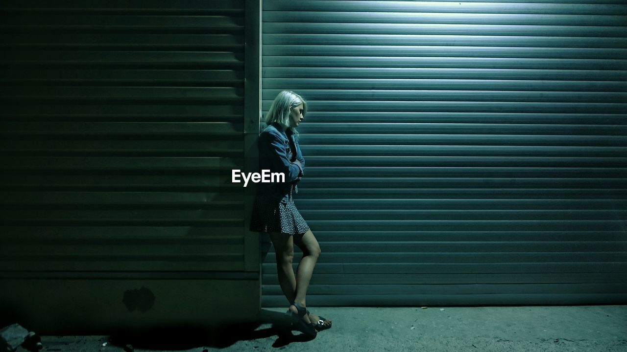Full Length Of Sad Young Woman Standing By Closed Shutter At Night