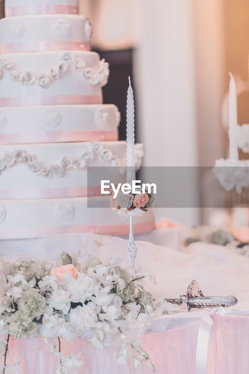 Close-Up Of Candle And Wedding Cake On Table