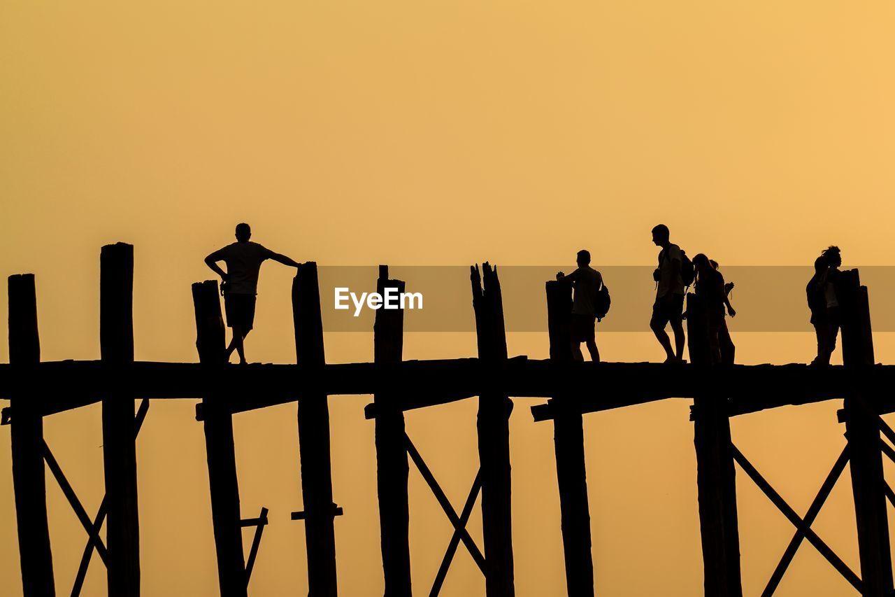 Silhouette people on pier against clear orange sky