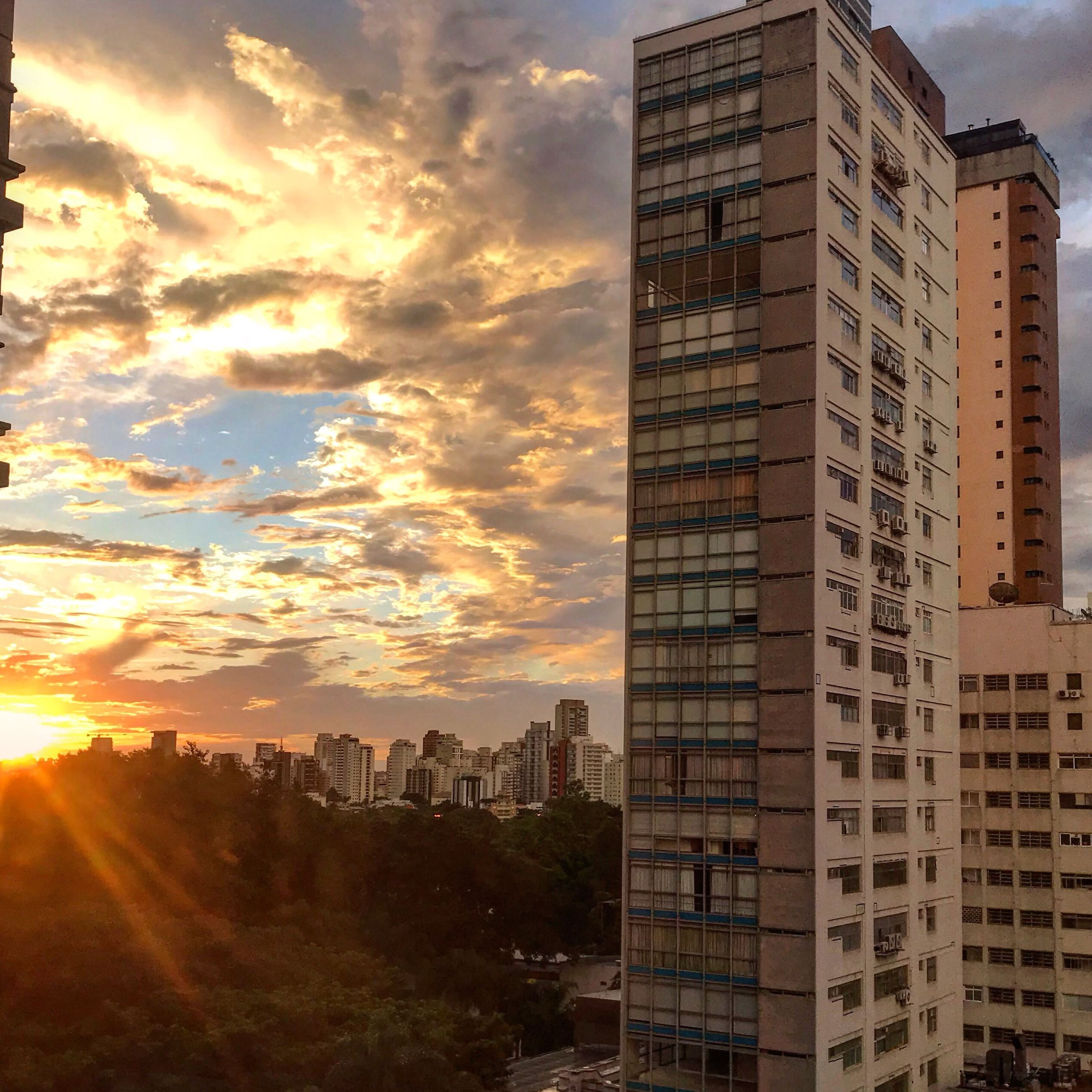 building exterior, architecture, built structure, city, building, sky, cloud - sky, sunset, office building exterior, nature, residential district, no people, cityscape, modern, tall - high, skyscraper, sunlight, office, outdoors, orange color, apartment