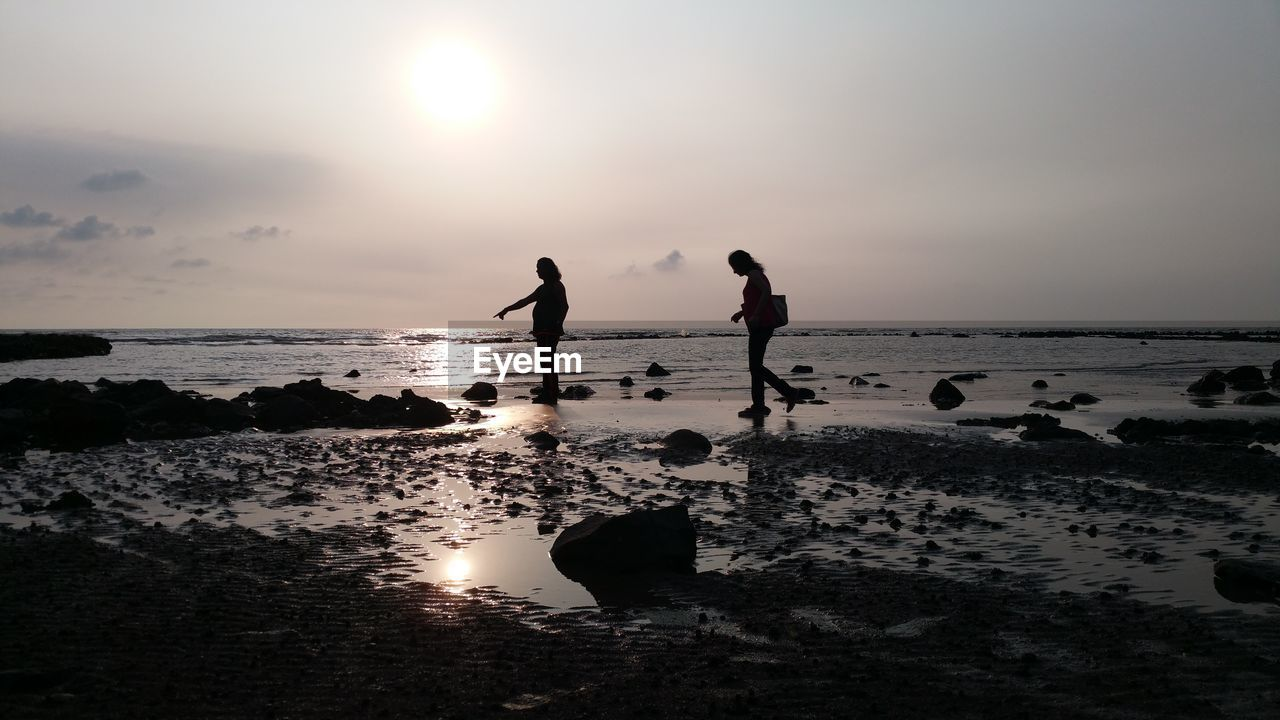 water, sky, sea, beach, land, silhouette, real people, sunset, horizon over water, sun, beauty in nature, horizon, men, scenics - nature, leisure activity, lifestyles, nature, two people, rock, outdoors