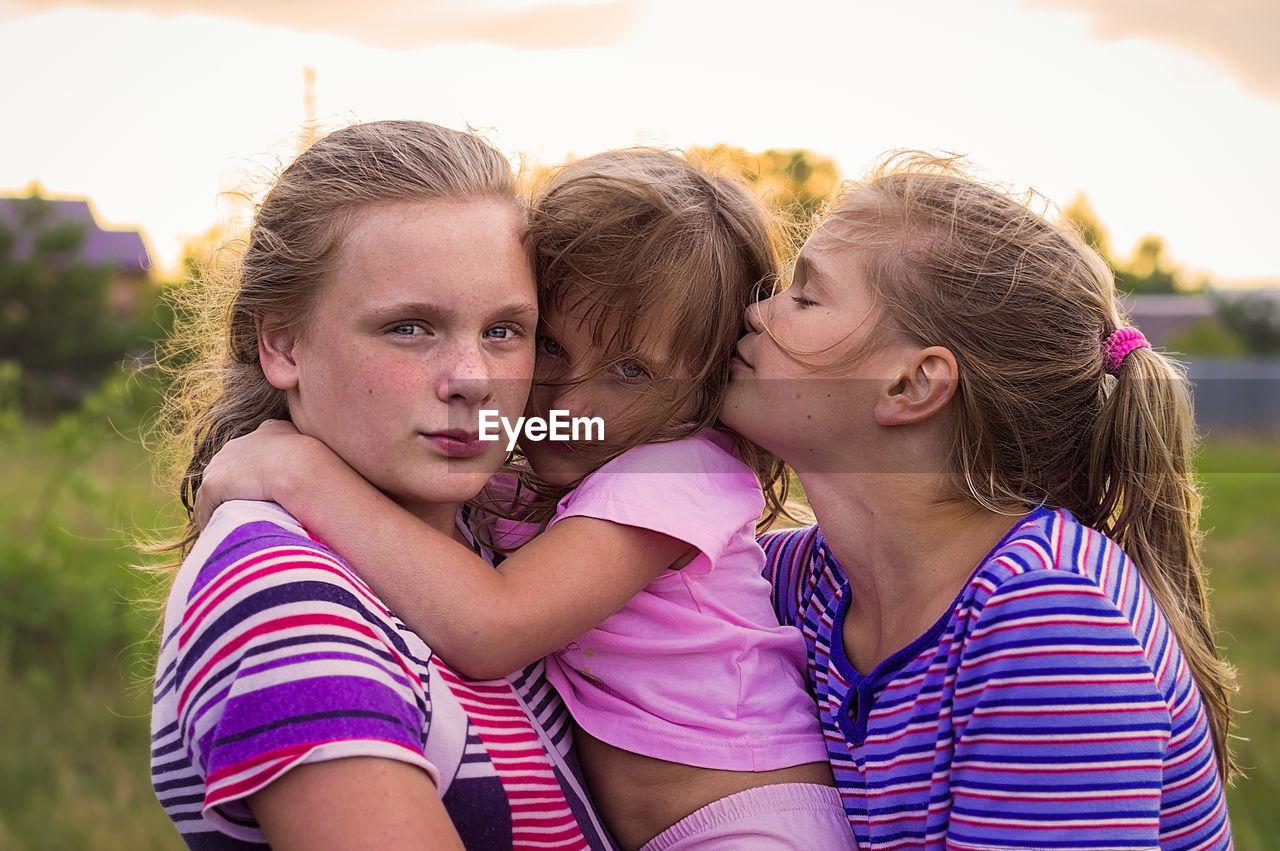 Portrait of siblings with girl against sky