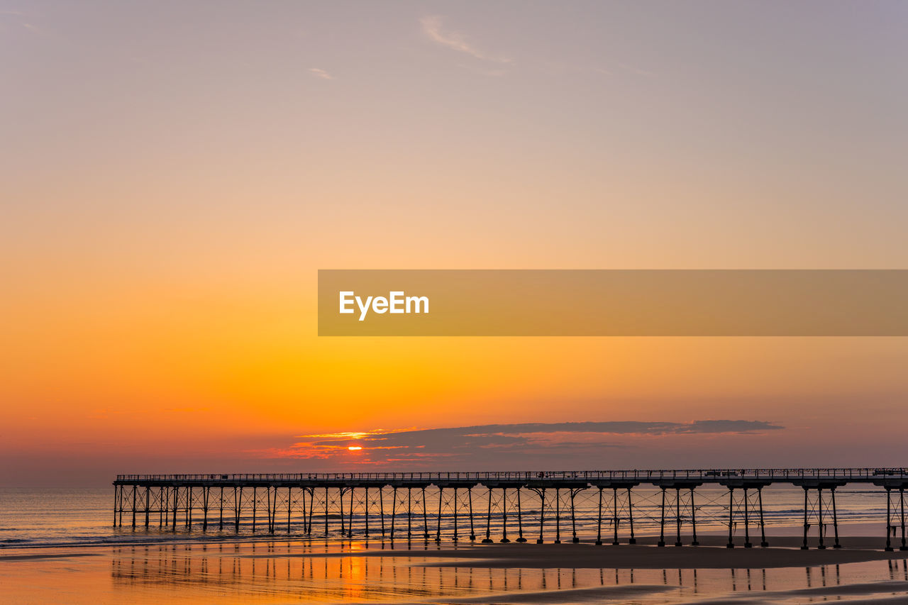 sky, sunset, water, orange color, beauty in nature, scenics - nature, sea, tranquility, tranquil scene, nature, no people, idyllic, copy space, non-urban scene, built structure, cloud - sky, horizon over water, outdoors, waterfront