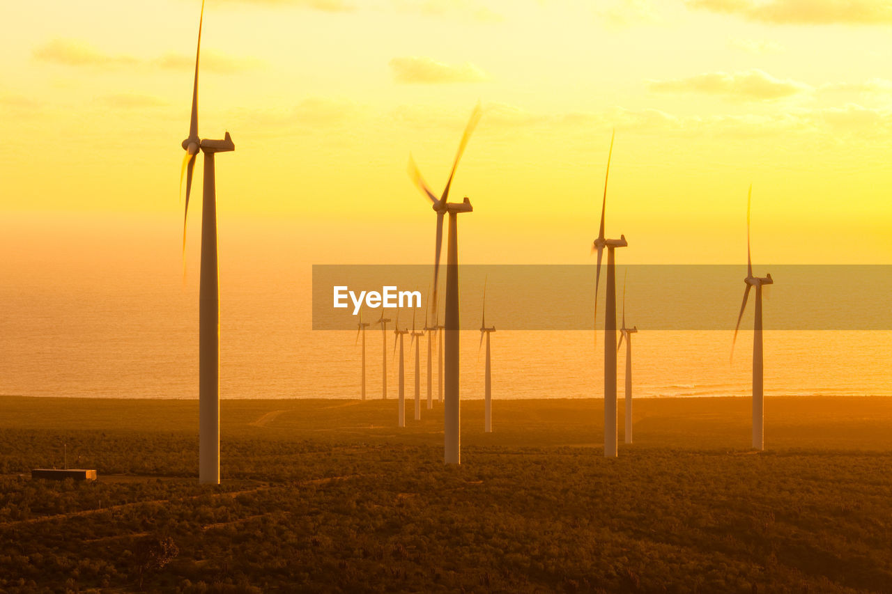 Windmills On Field By Sea Against Sky During Sunset