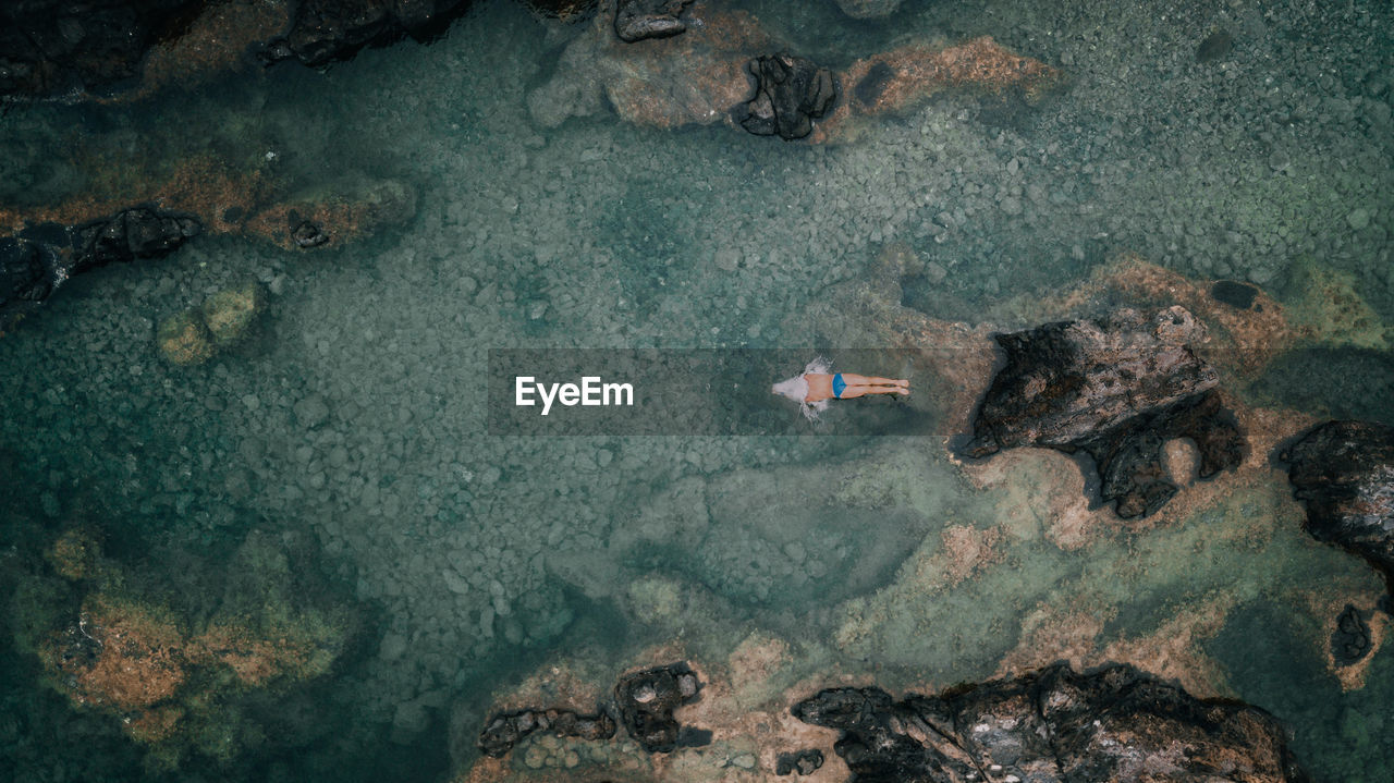 Drone view of man swimming in sea