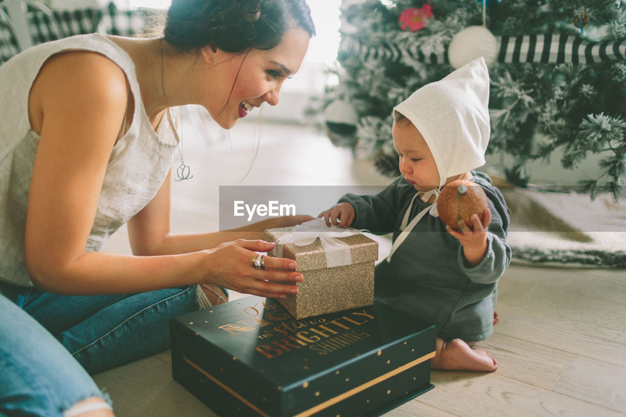 Mother showing christmas present white sitting at home
