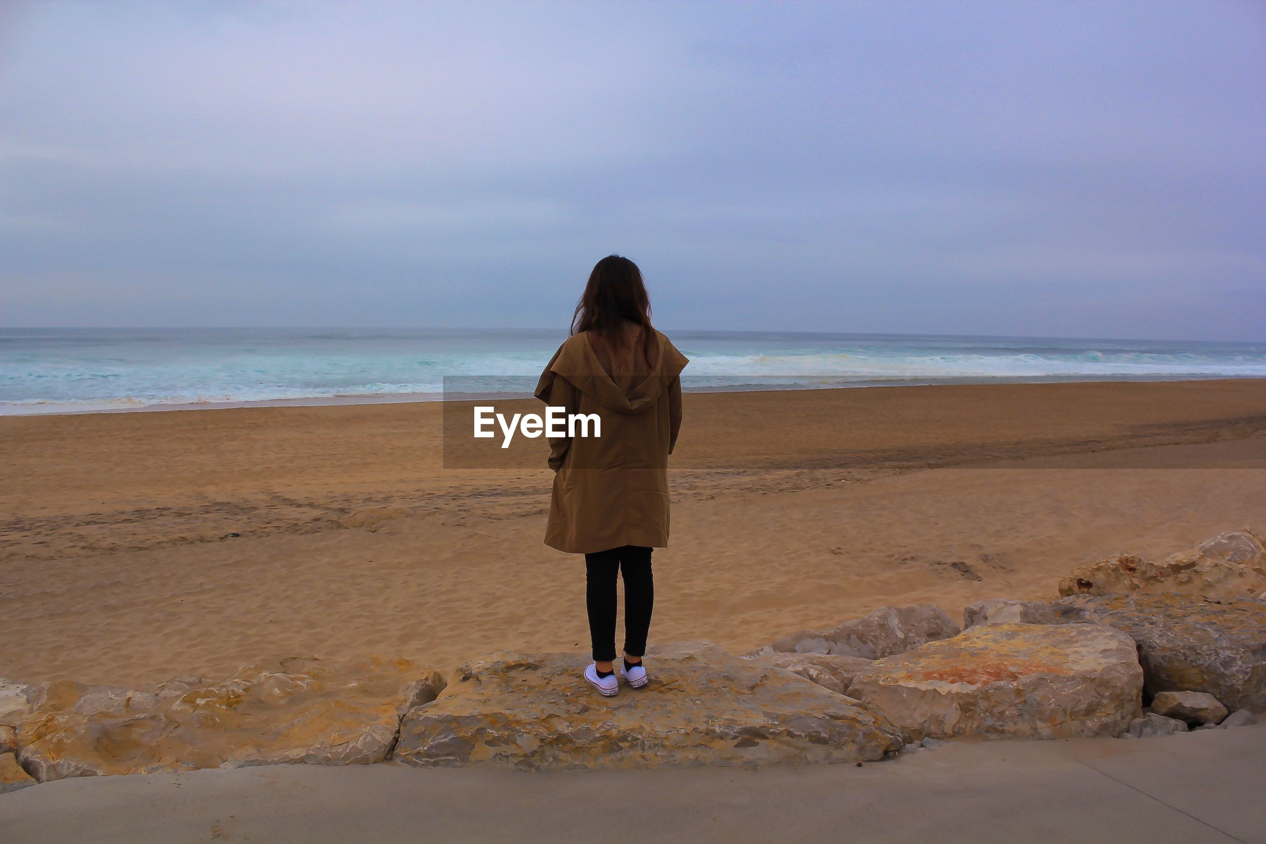 Rear view of woman looking at seascape while standing on rock