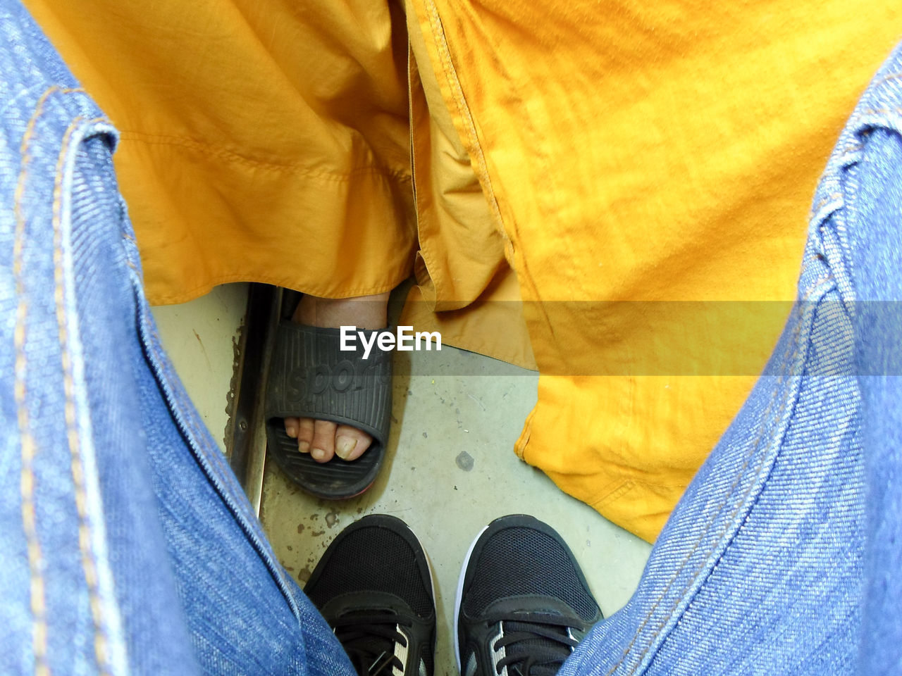 low section, shoe, human leg, human body part, one person, real people, body part, personal perspective, standing, lifestyles, jeans, textile, blue, casual clothing, denim, yellow, high angle view, unrecognizable person, leisure activity, human foot, outdoors, human limb