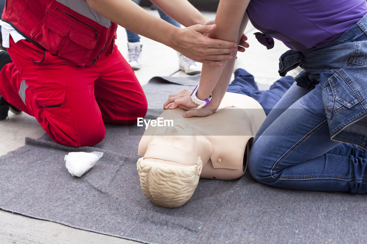 Midsection Of Instructor Teaching Paramedic While Performing Cpr On Dummy