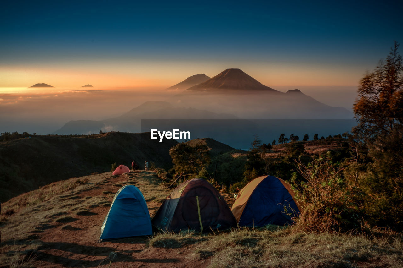 sky, mountain, tent, camping, environment, nature, beauty in nature, adventure, sunset, land, scenics - nature, landscape, tranquility, tranquil scene, leisure activity, exploration, non-urban scene, people, travel, outdoors, mountain peak