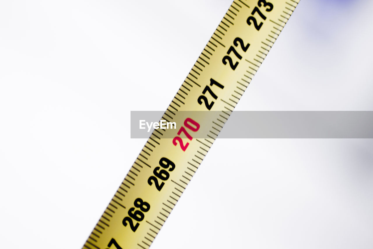 number, copy space, white background, close-up, indoors, no people, accuracy, studio shot, still life, instrument of measurement, single object, nature, tape measure, cut out, scale, yellow, wood - material, communication, high angle view, western script