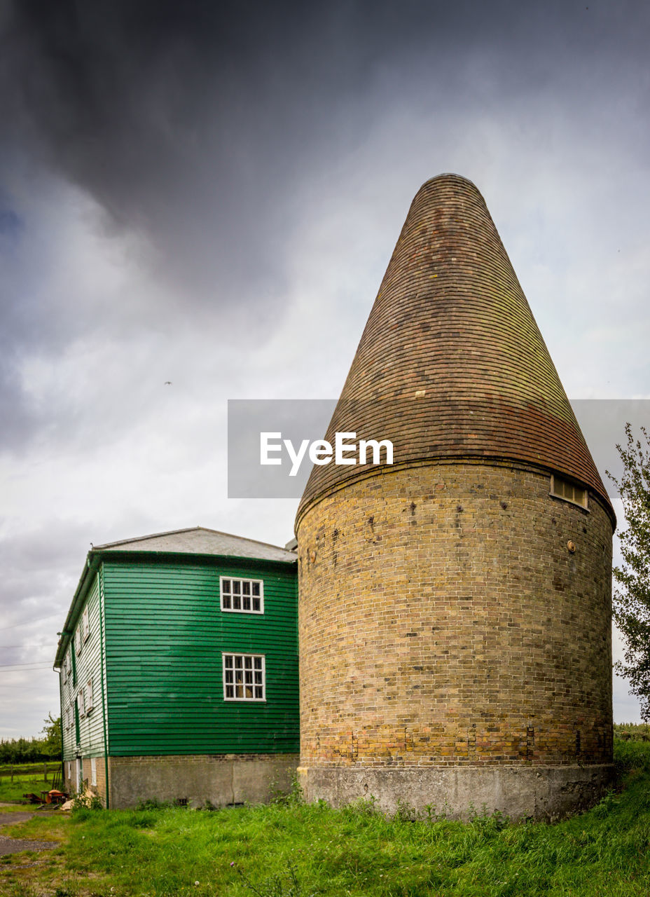 built structure, architecture, cloud - sky, sky, building exterior, no people, building, day, nature, outdoors, green color, grass, factory, plant, land, wall - building feature, landscape, low angle view, field, tower