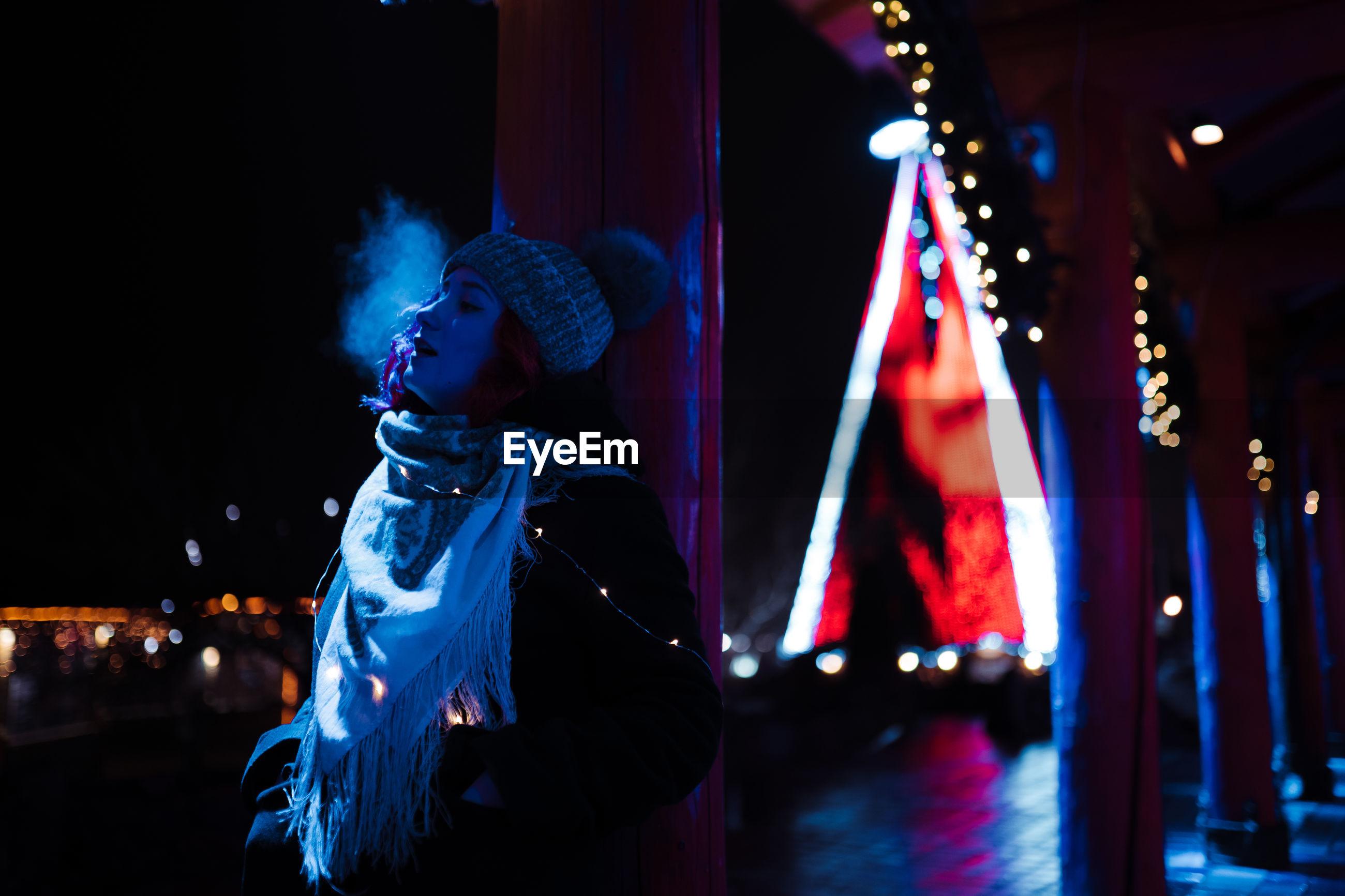 Woman looking at illuminated stage at night