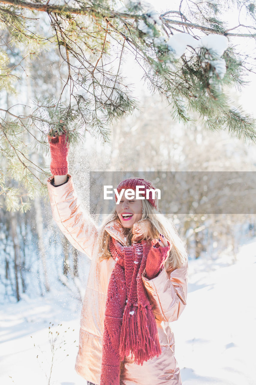 Happy Young Woman Enjoying By Trees On Snowy Field In Winter