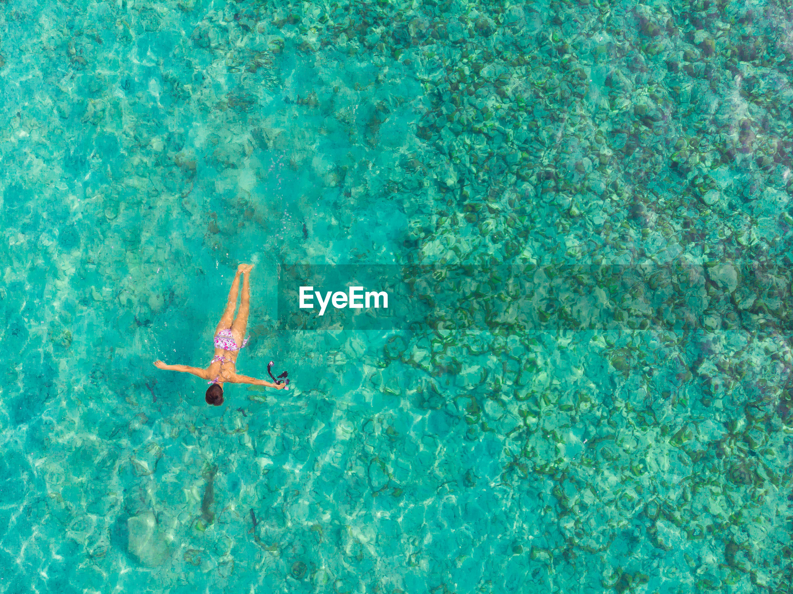 High angle view of woman wearing bikini swimming in sea