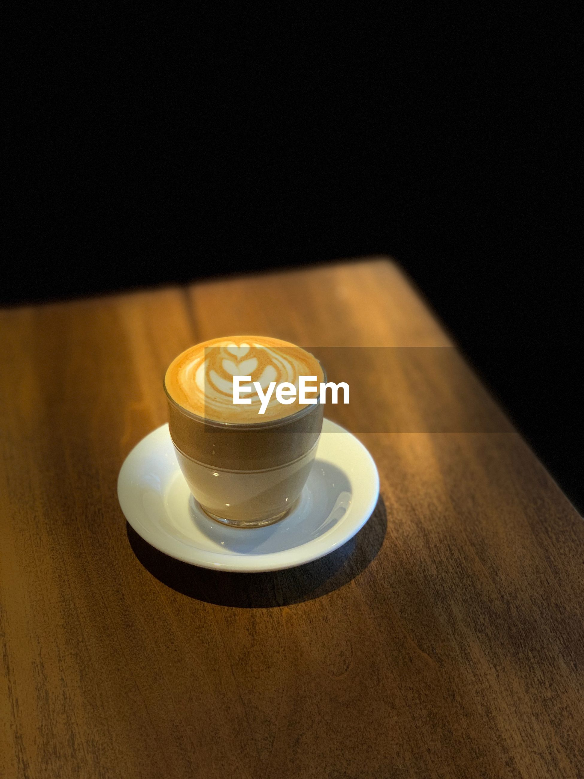 COFFEE CUP ON TABLE WITH BLACK BACKGROUND