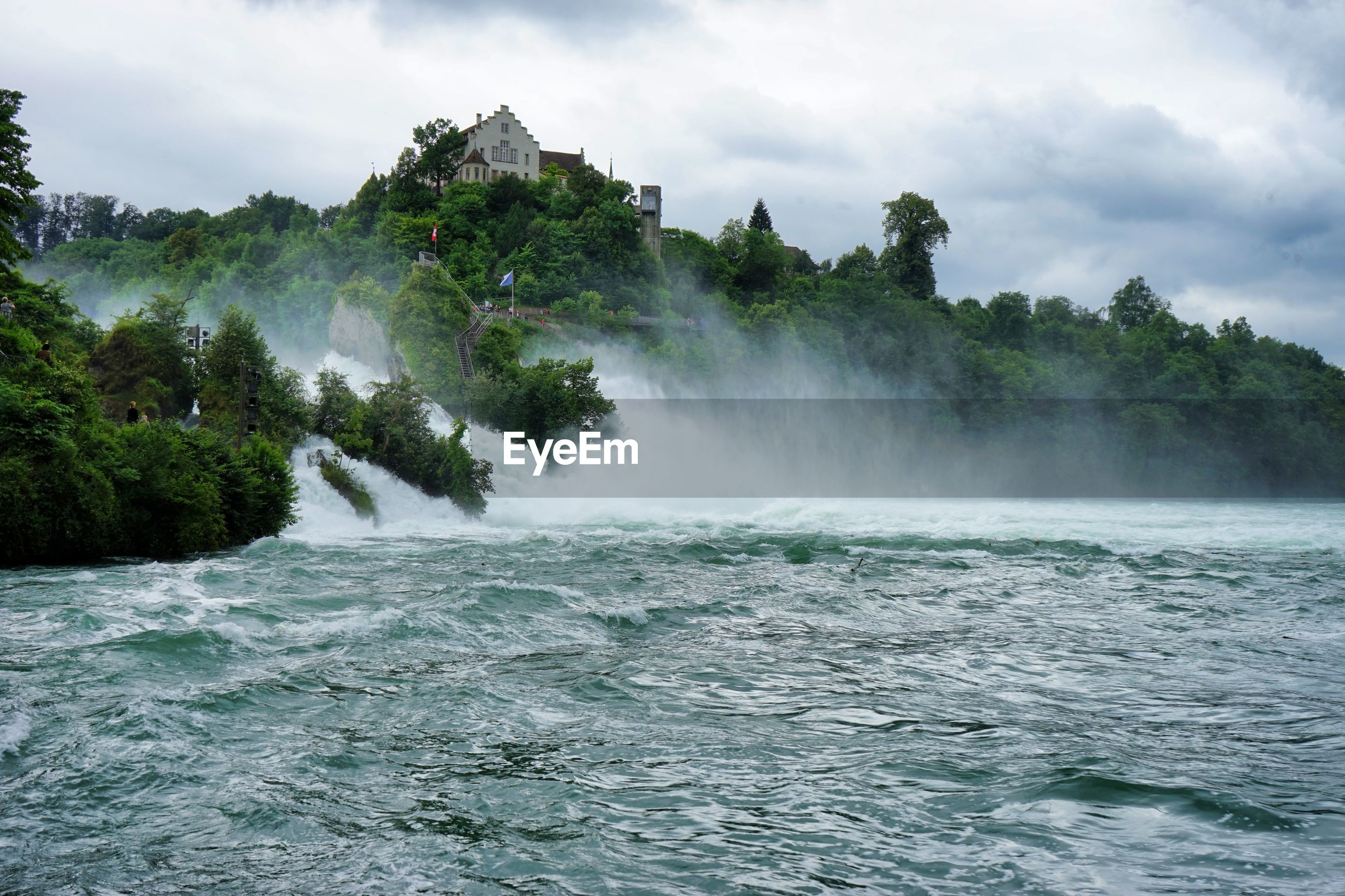 Scenic view of river and trees against cloudy sky