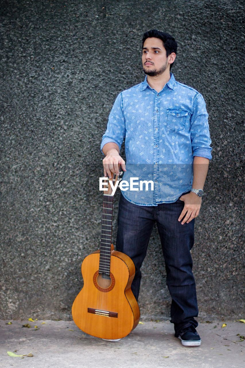Full length of young man with guitar standing against wall