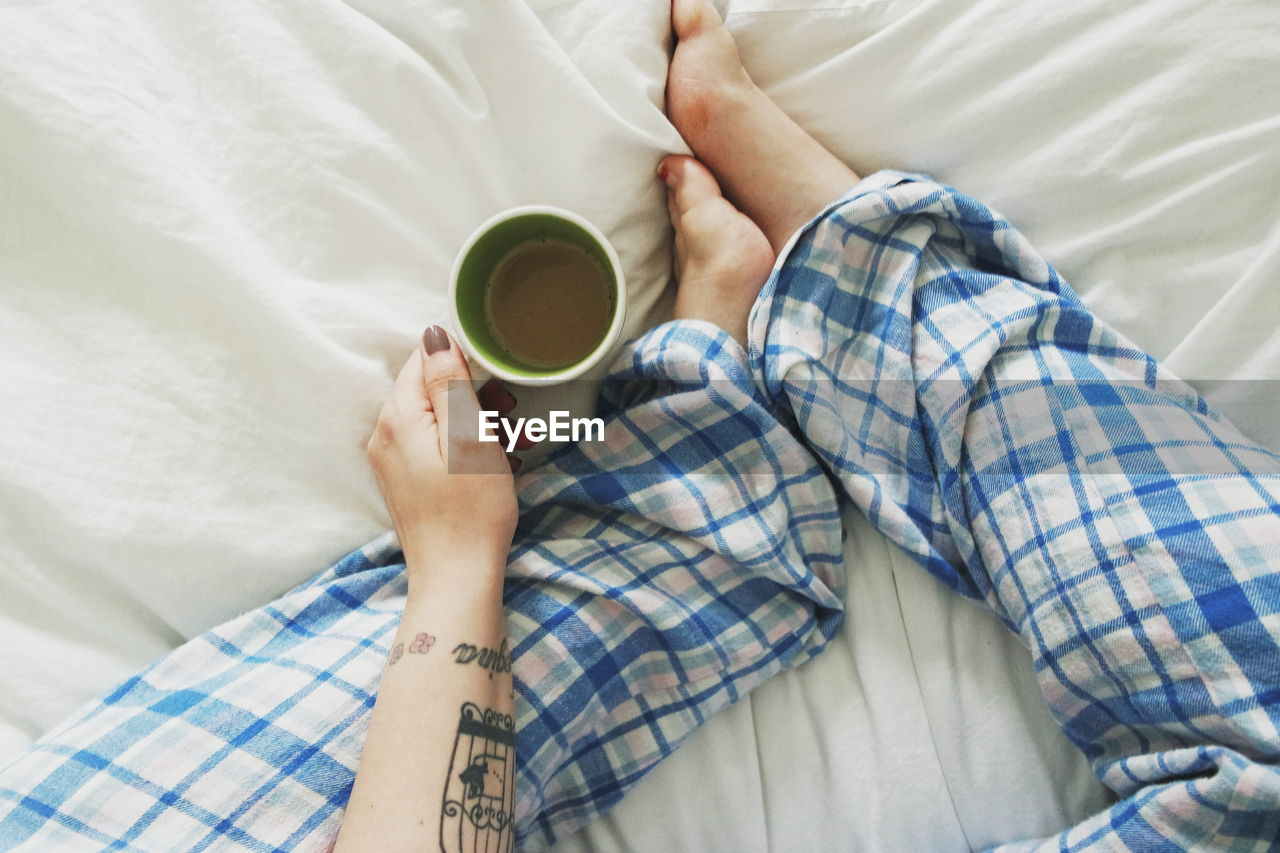 Woman relaxing in bed with tea
