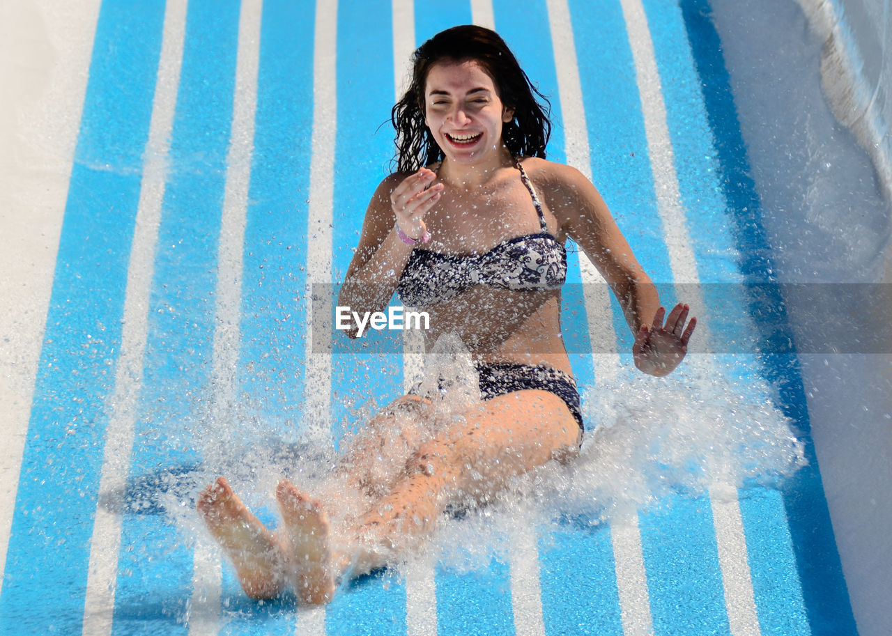 Portrait Of Smiling Young Woman On Water Slide