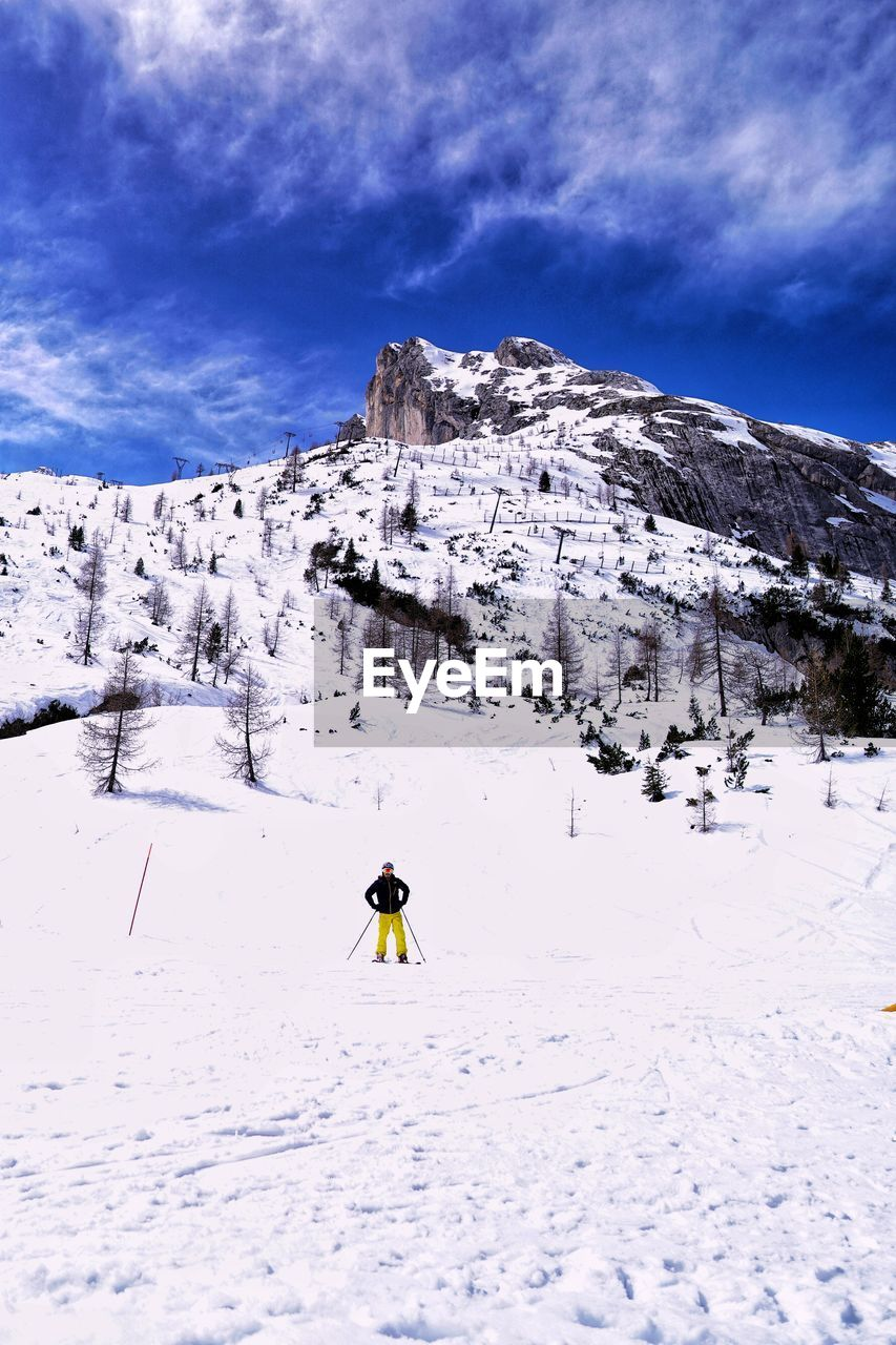 cold temperature, mountain, winter, beauty in nature, snow, sky, leisure activity, real people, one person, scenics - nature, cloud - sky, lifestyles, adventure, snowcapped mountain, mountain range, white color, covering, winter sport, sport, outdoors, ski-wear
