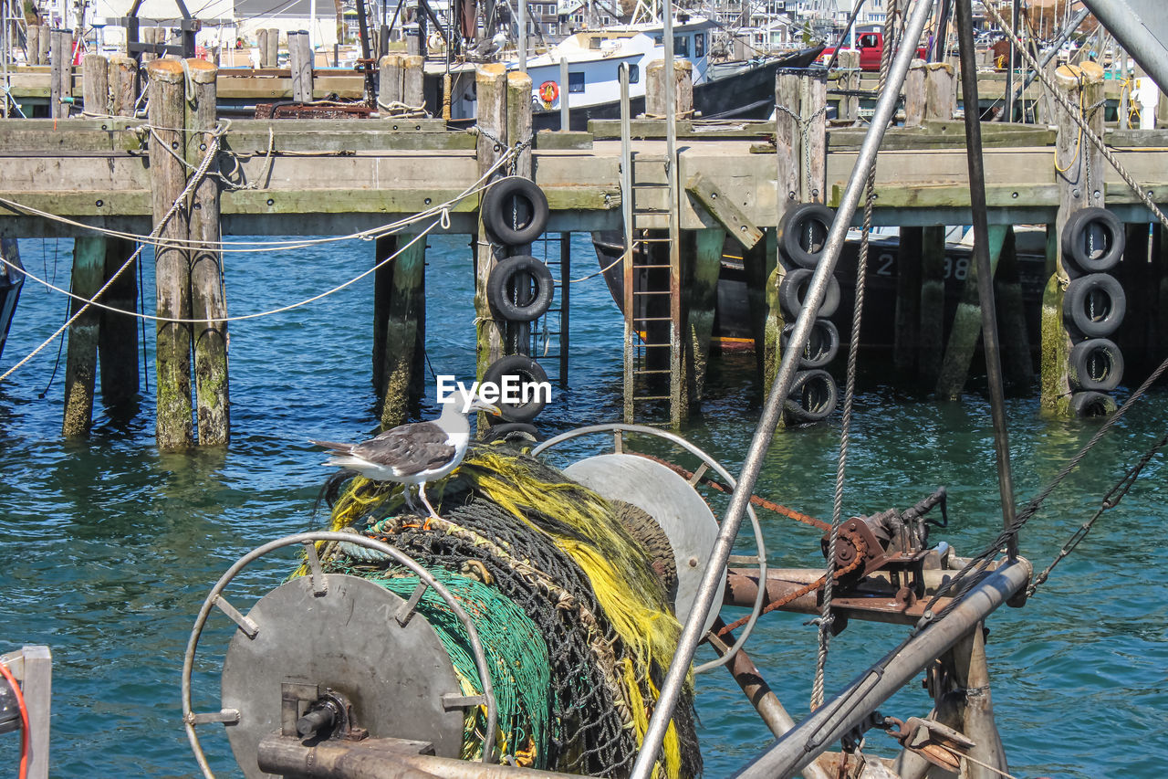 water, nautical vessel, transportation, sea, day, mode of transportation, rope, metal, nature, no people, outdoors, fishing, moored, architecture, connection, harbor, high angle view, fishing industry, fishing boat, wheel
