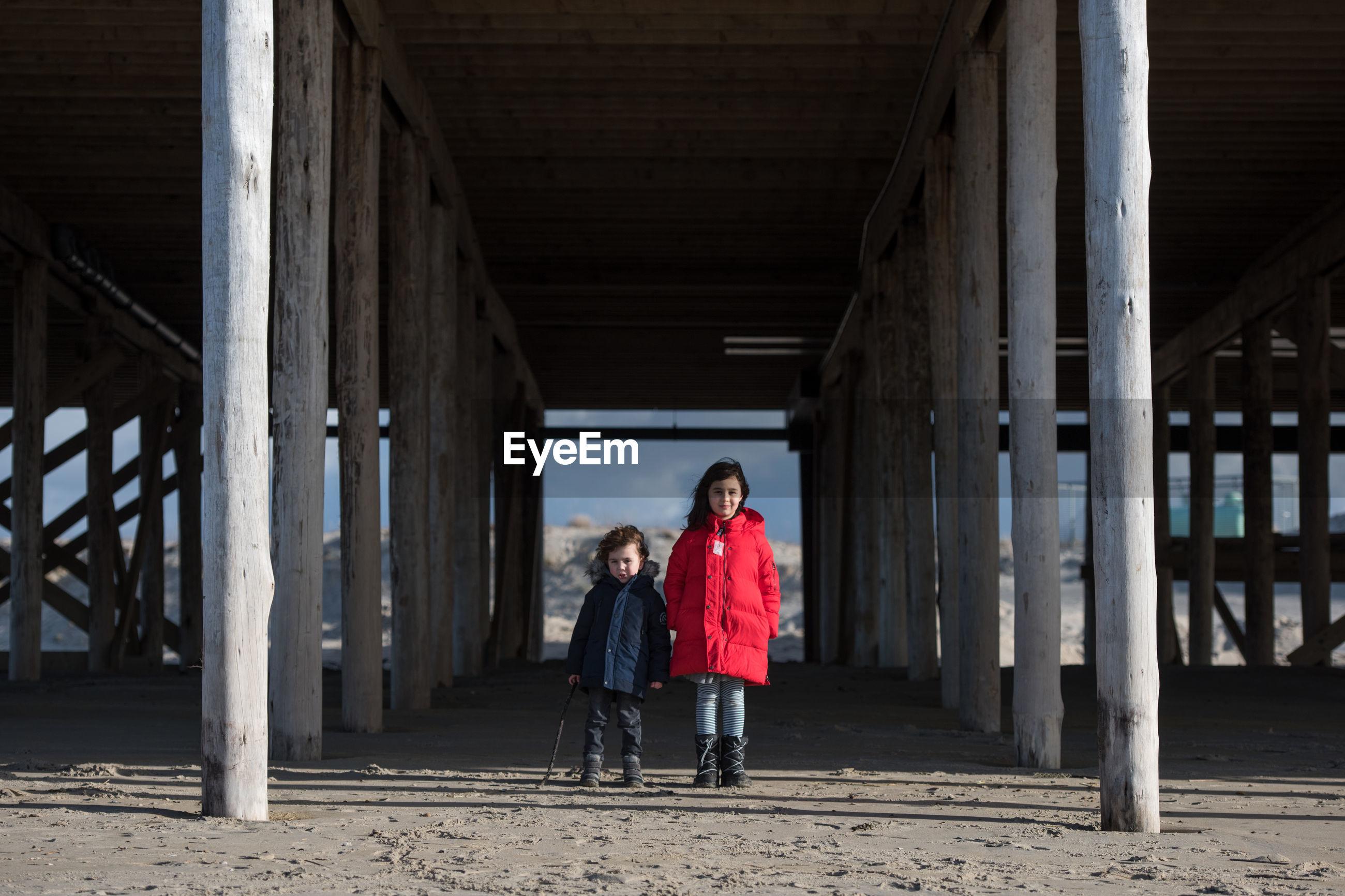 Full length of siblings standing under bridge at beach