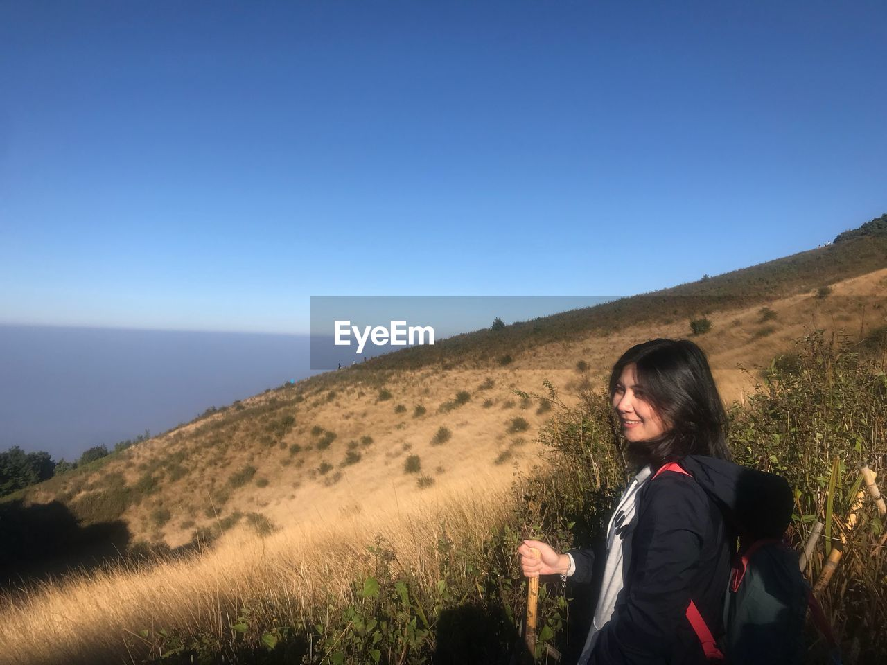 Smiling woman looking away while standing on mountain