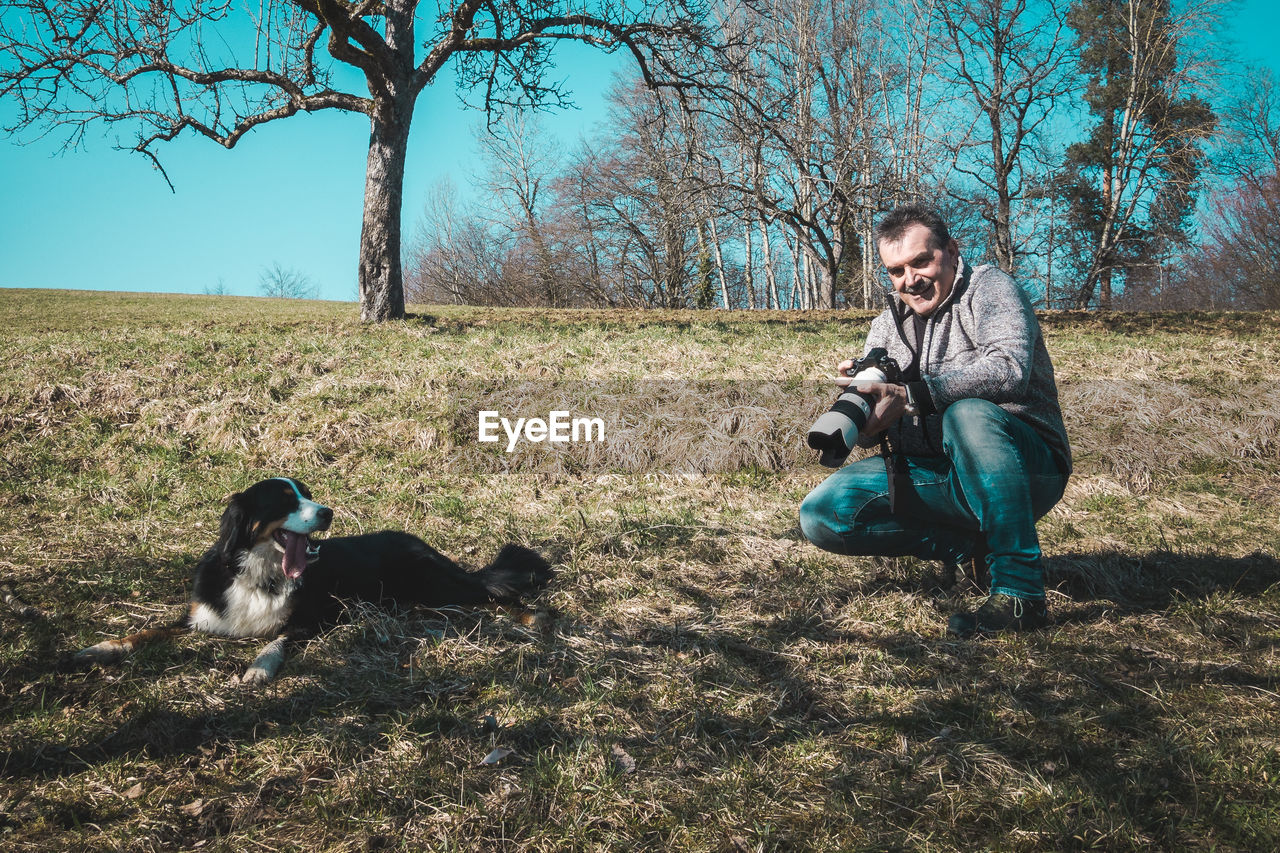 Man Photographing Dog On Field Against Trees