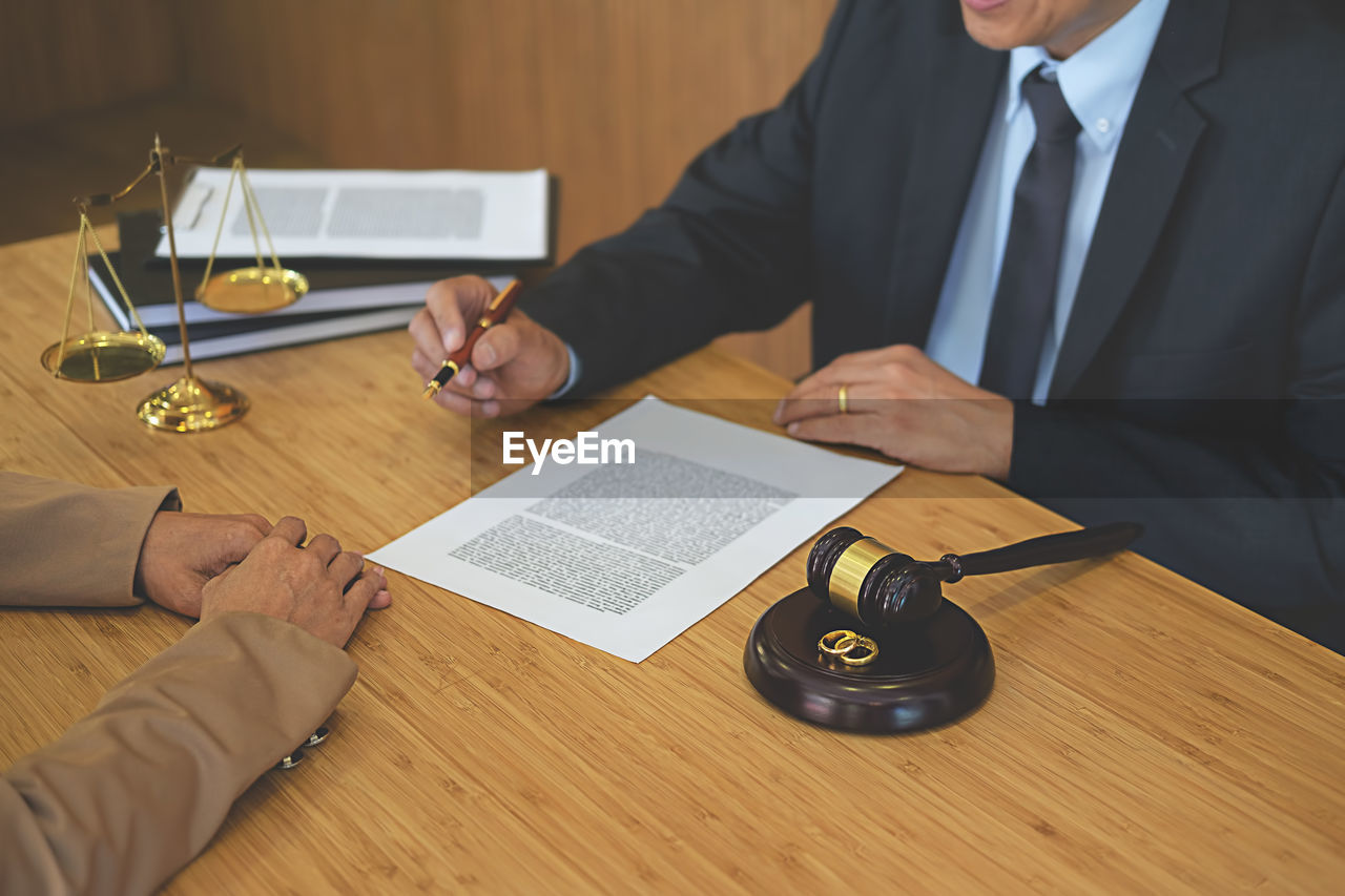Close-up of judge and client discussing on table