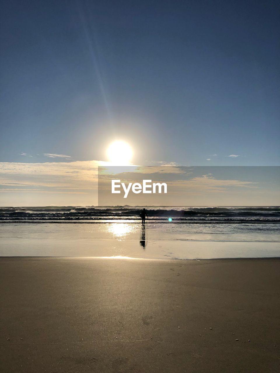 sky, water, scenics - nature, beauty in nature, land, beach, sea, tranquil scene, tranquility, sun, sunlight, horizon, horizon over water, nature, idyllic, non-urban scene, sunset, reflection, silhouette, outdoors, lens flare, bright