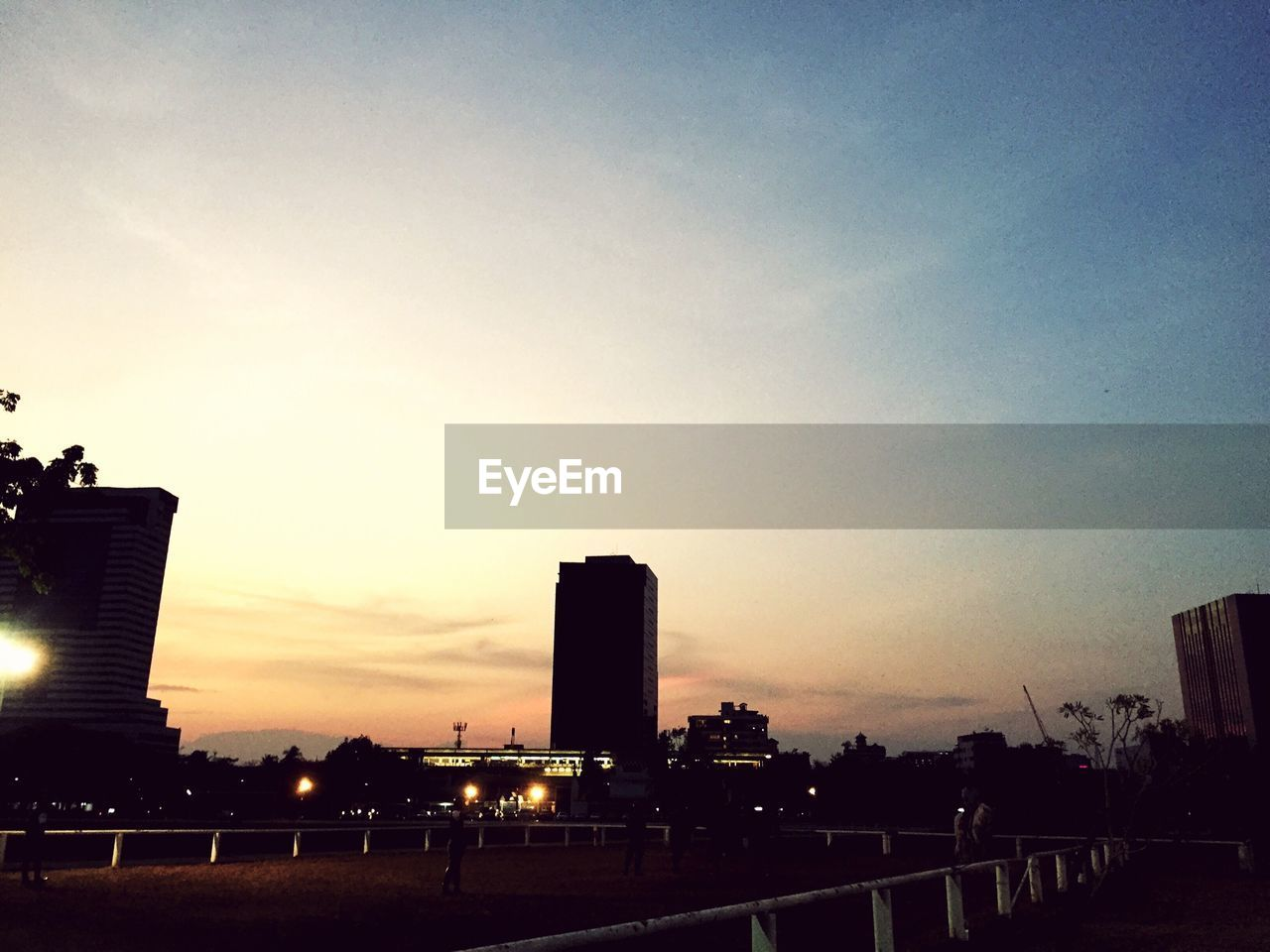 sunset, architecture, silhouette, built structure, building exterior, city, skyscraper, sky, outdoors, no people, modern, tree, day