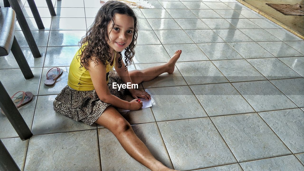 Portrait Of Cute Girl Sitting On Tiled Floor At Home