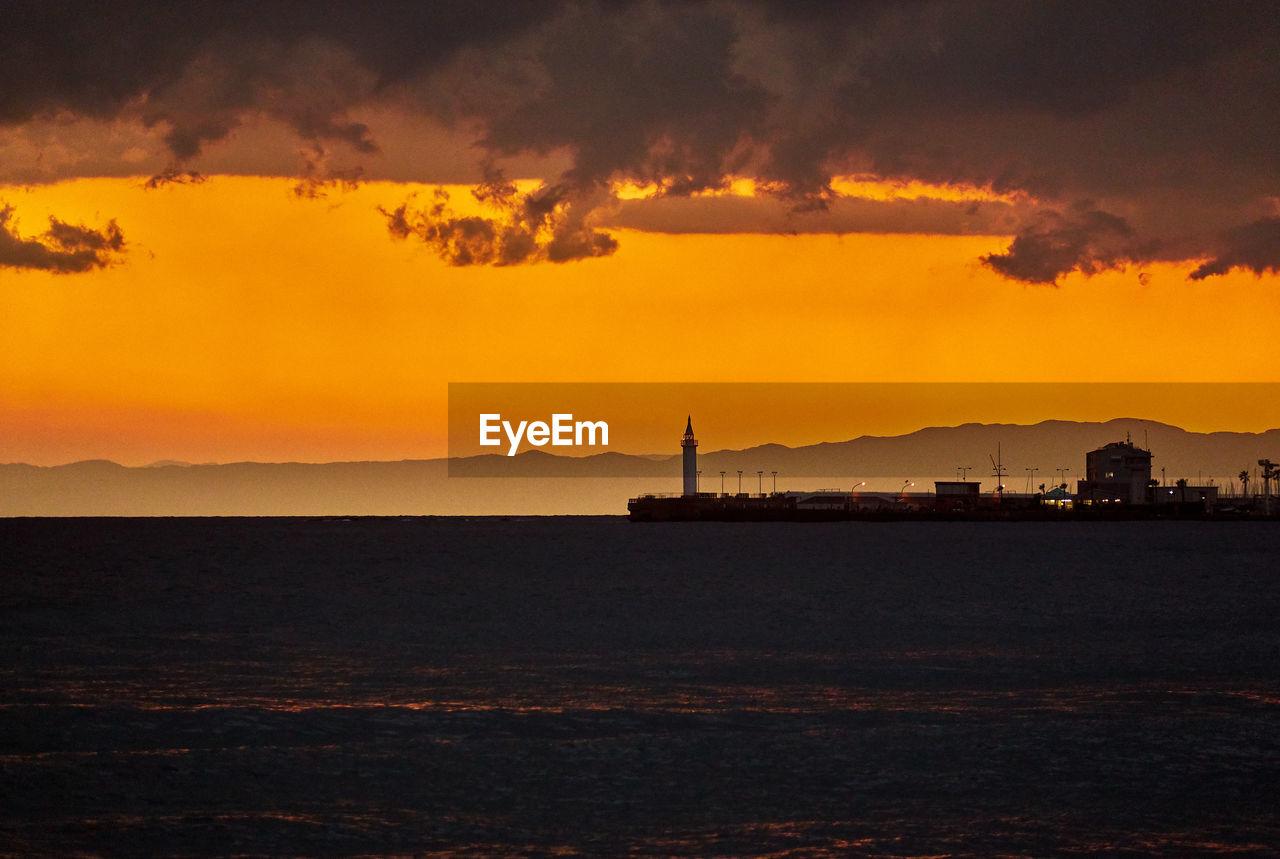 Silhouette pier by sea against orange sky