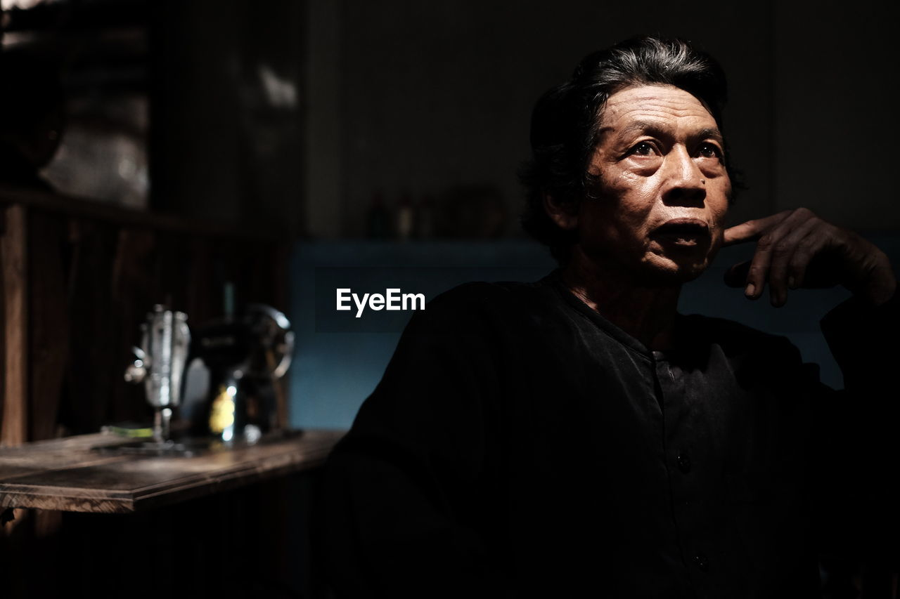 Thoughtful mature man sitting in darkroom