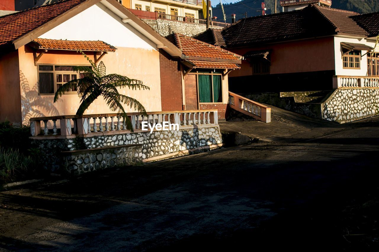 building exterior, architecture, built structure, house, residential building, roof, sunlight, day, shadow, outdoors, no people, tiled roof, city, sky