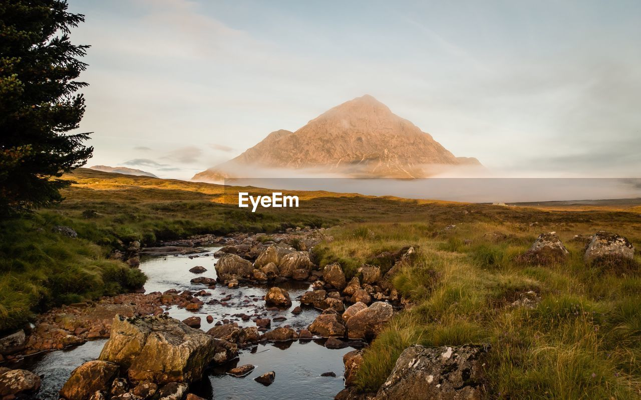 Rocks On Stream By Field Against Buachaille Etive Mor In Foggy Weather