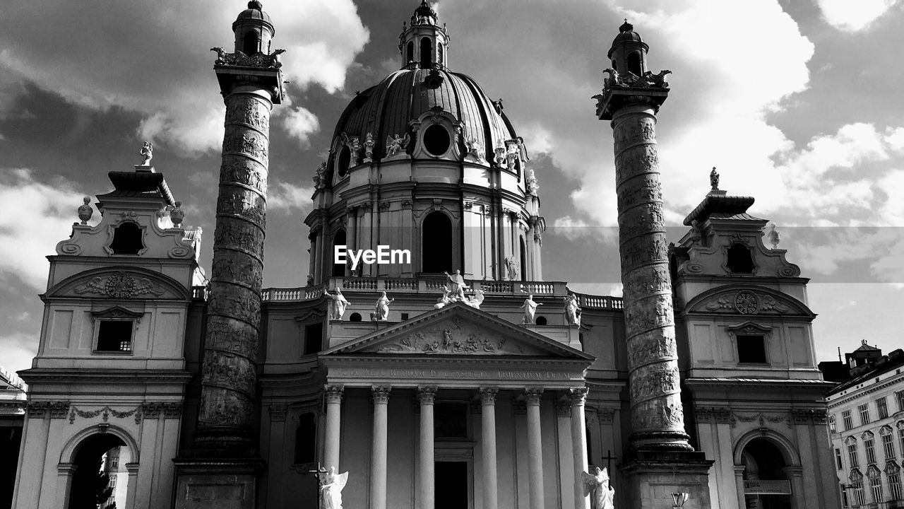 architecture, building exterior, religion, built structure, dome, spirituality, architectural column, place of worship, sky, low angle view, cloud - sky, outdoors, statue, facade, history, day, travel destinations, no people, city