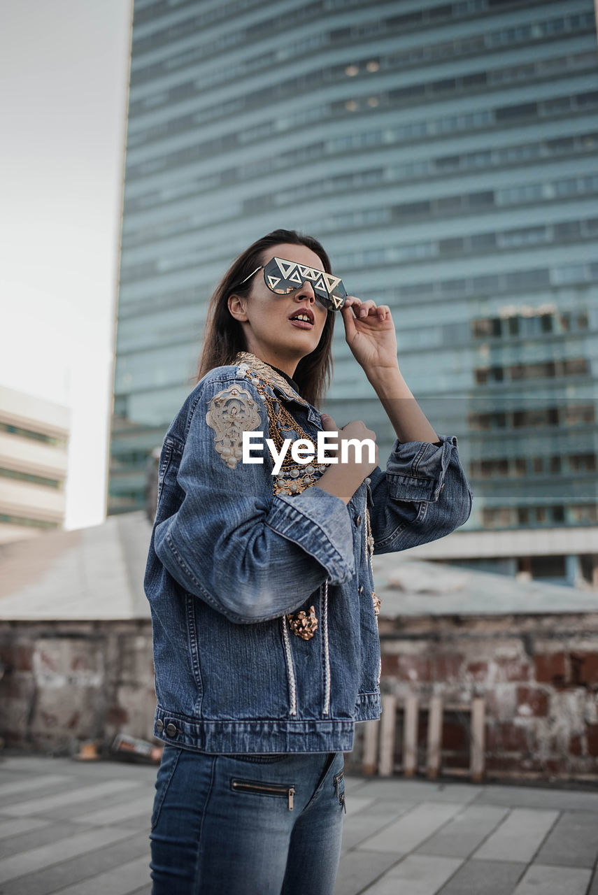 Young Woman Wearing Sunglasses While Standing Against Building In City