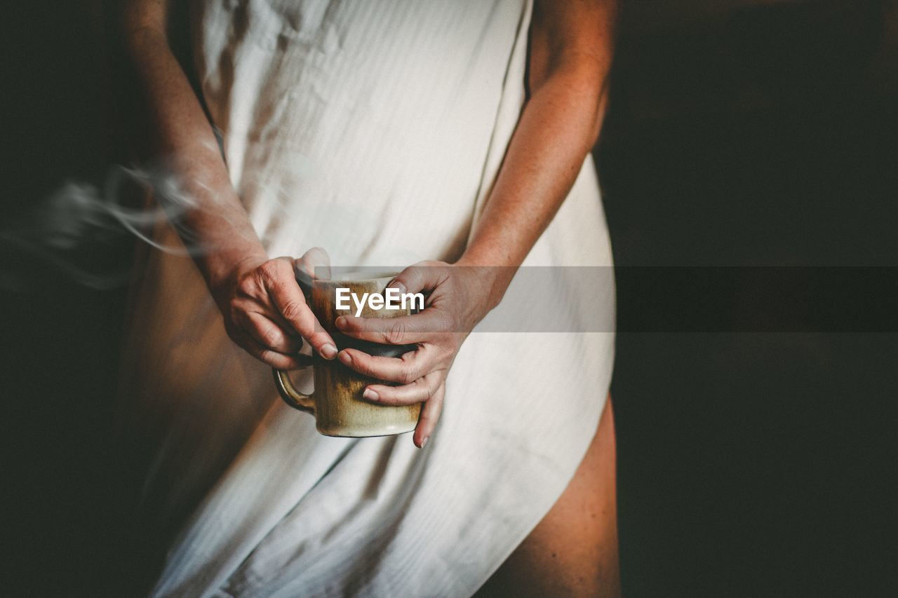 Midsection Of Woman Holding Coffee Over Black Background