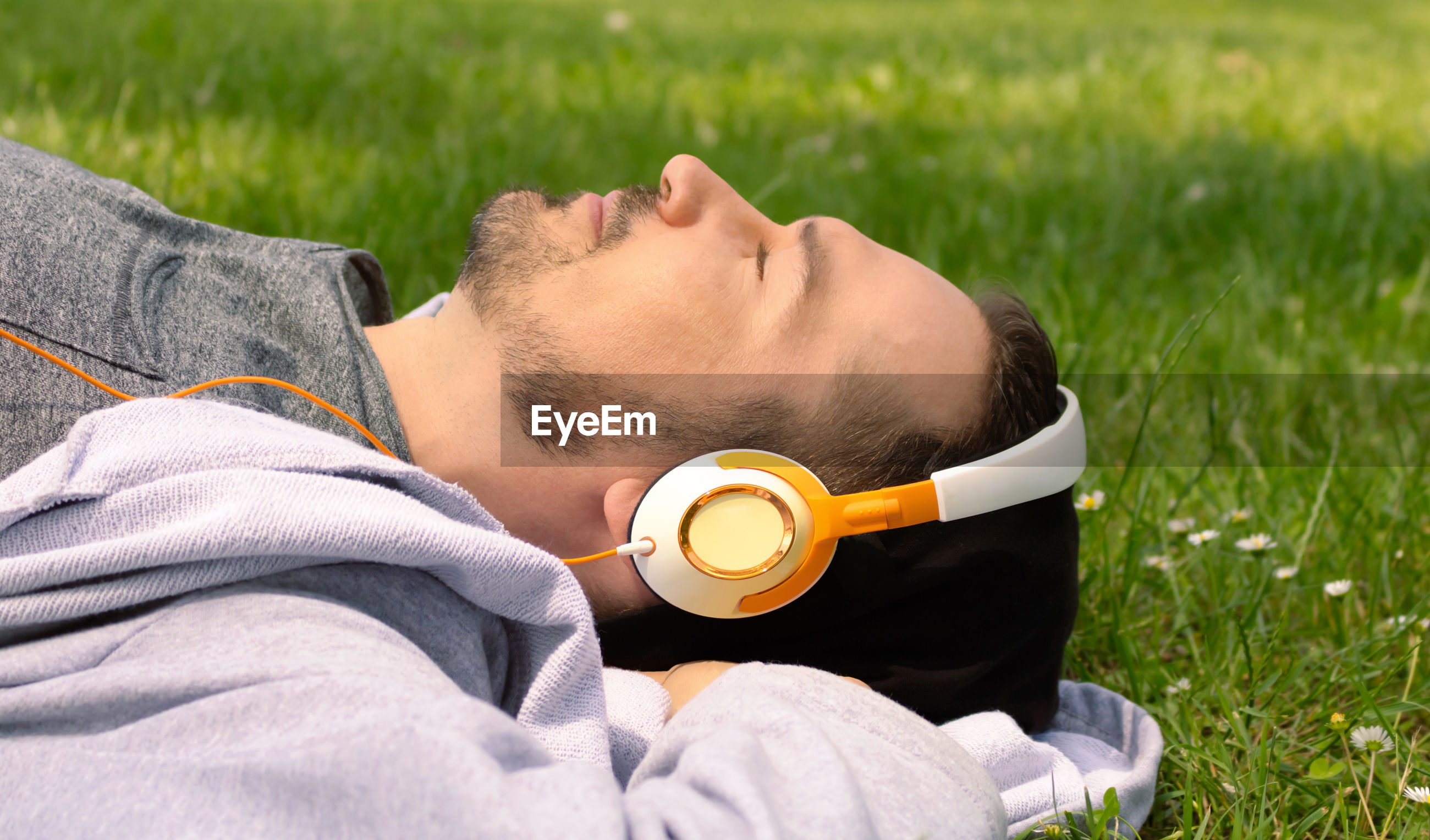 YOUNG MAN LYING ON FIELD